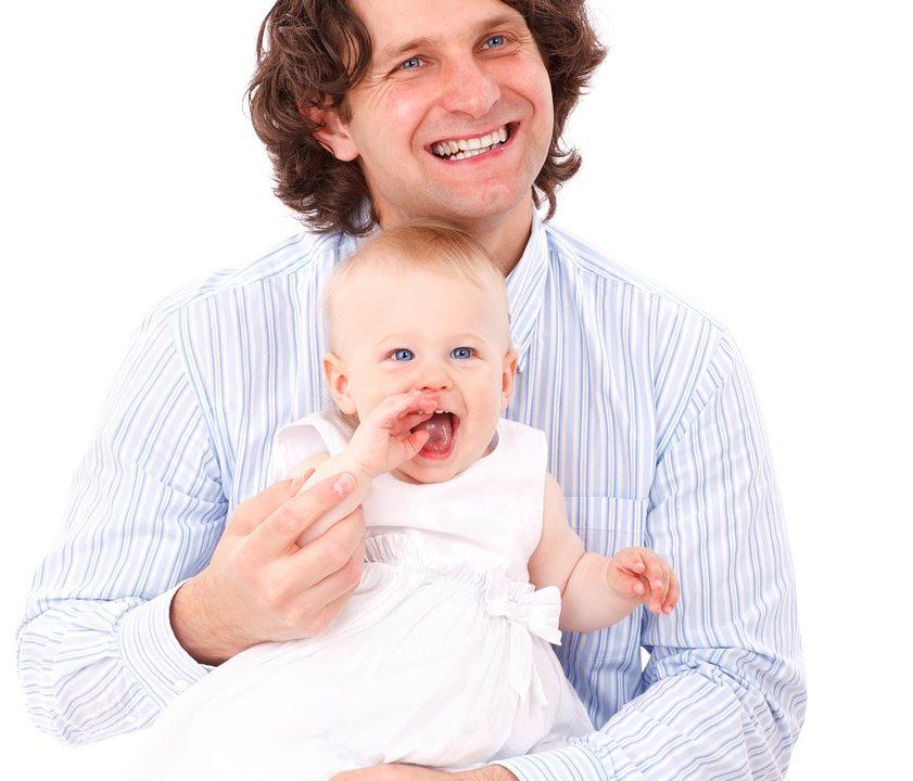子供を抱きかかえながら微笑むパパ